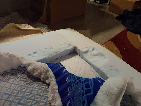 Picture of a corner of buckling gel being extracted from a mattress topper